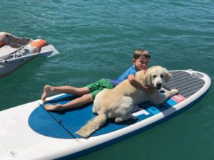 Little kid Mason beside a white dog in a surf baord floating on blue waters